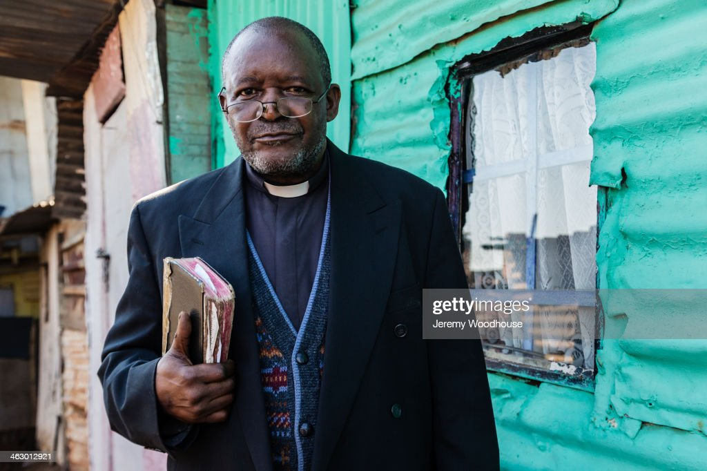 Black priest carrying bible : Stock Photo