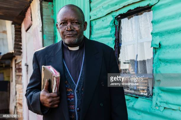 black priest carrying bible - priest stock pictures, royalty-free photos & images