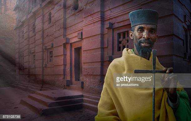 black priest carrying cross in lalibela, ethiopia - lalibela stock photos and pictures