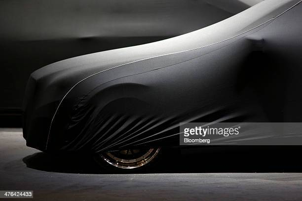 Black protective cover sits over a luxury automobile on the Binz GmbH & Co. Display stand ahead of the opening day of the 84th Geneva International...