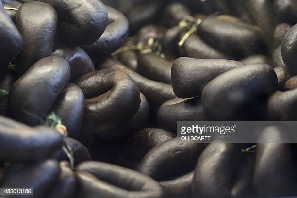Black puddings are displayed for sale on a stall in the open section of Bury Market in Bury northern England on August 5 2015 Bury Market which has...