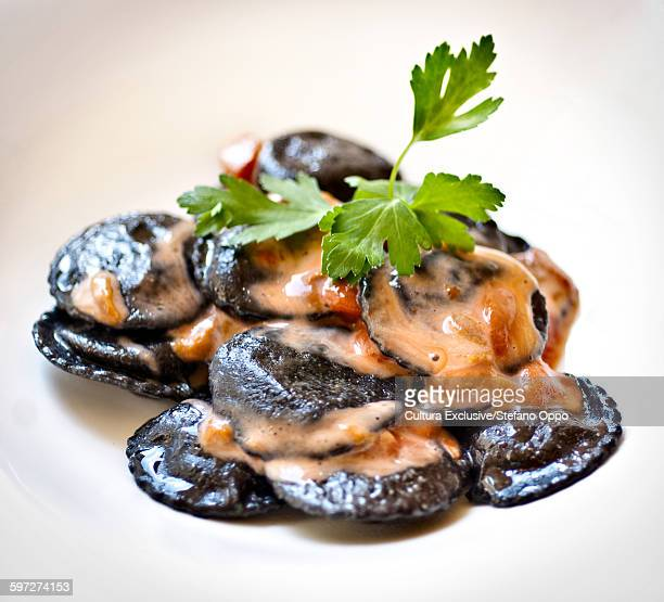 Black ravioli stuffed with fish and served with sea urchin