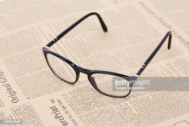 black reading glasses on a newspaper - occhiali da lettura foto e immagini stock