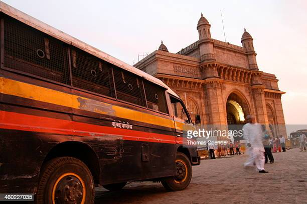 Black, red and orange police van is stationed next to the Gateway to India arch at dusk in Mumbai. The site is near the Taj Mahal Palace Hotel which...