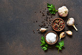 Black, red and white peppersalt, salt, garlic in a wooden bowl . Classic spices for cooking. View from above.