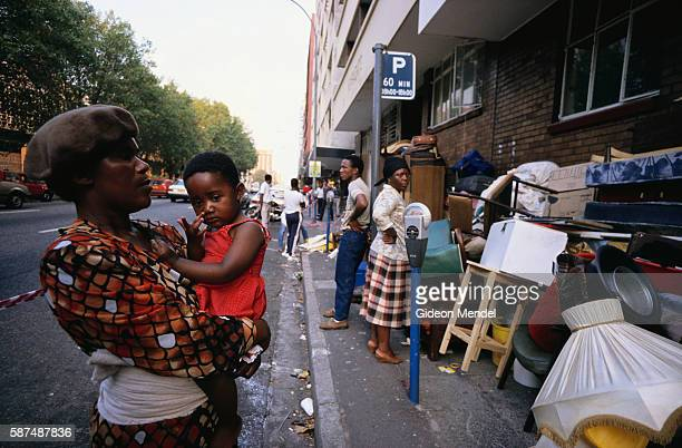 Black residents stand on the sidewalks with their belongings after being evicted during rent disputes in the all white Hillbrow neighborhood of...