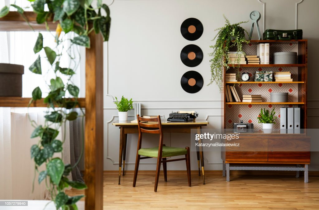 Black retro typewriter on a unique wooden desk, a mid-century modern chair and a renovated bookcase in a hipster home office interior. Real photo. : Stock Photo
