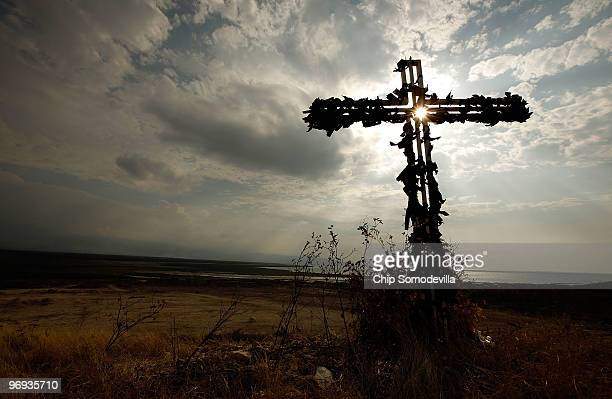 Black ribbons tied to a metal cross flutter in the wind on a hilltop above the mass grave site where many thousands of earthquake victims are buried...