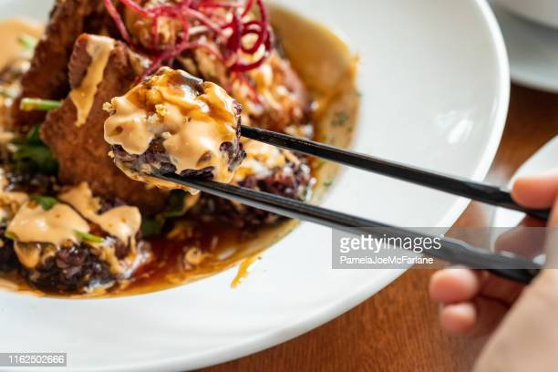 pov of black rice rock n roll sushi maki - extreme close up stock pictures, royalty-free photos & images