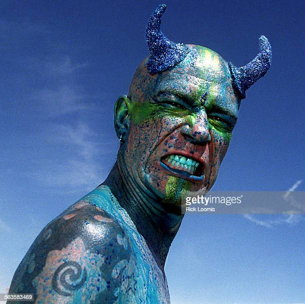 Black Rock City Nevada––Mark Day of Santa Cruz gets painted with blue food coloring to go with his blue devil horns while participating in this...