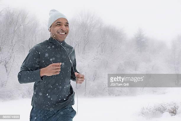 Black runner jogging in snow