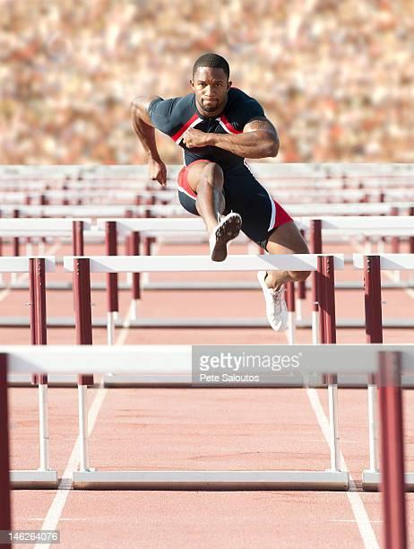 Black runner jumping hurdles in track race