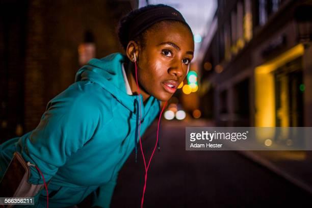 black runner resting on city street at night - black alley foto e immagini stock