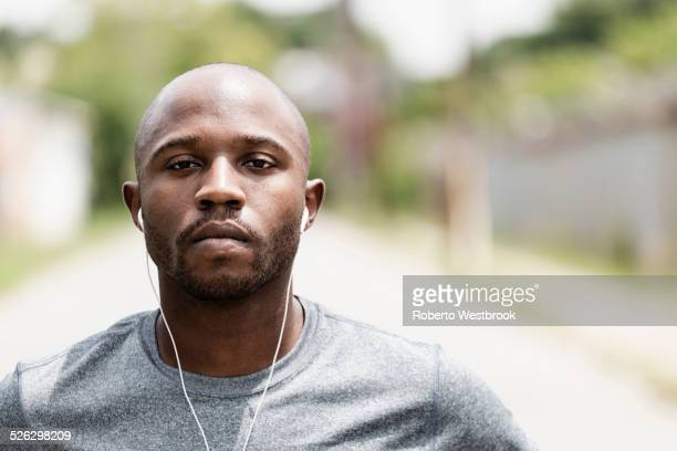 Black runner resting on city street with earbuds