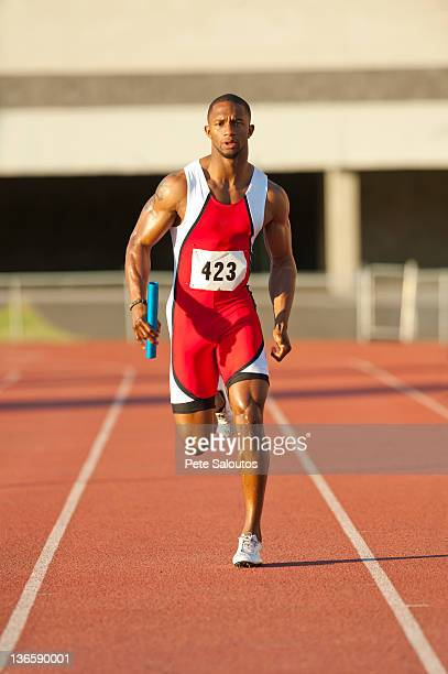 black runner running on track in relay race - athleticism stock pictures, royalty-free photos & images