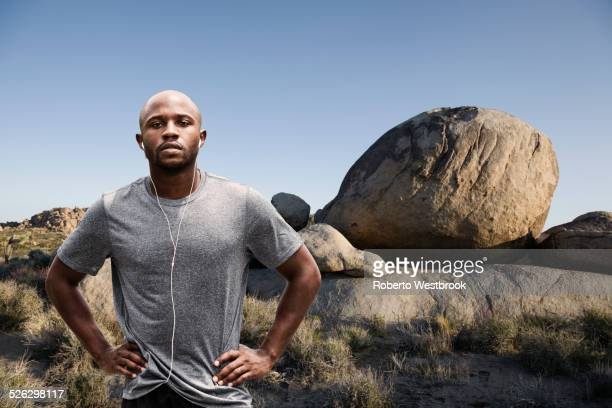 Black runner standing in rocky remote landscape