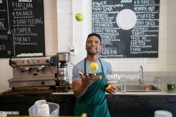 black salesman working at a cafe juggling with fruits behind the counter having fun - juggling stock pictures, royalty-free photos & images