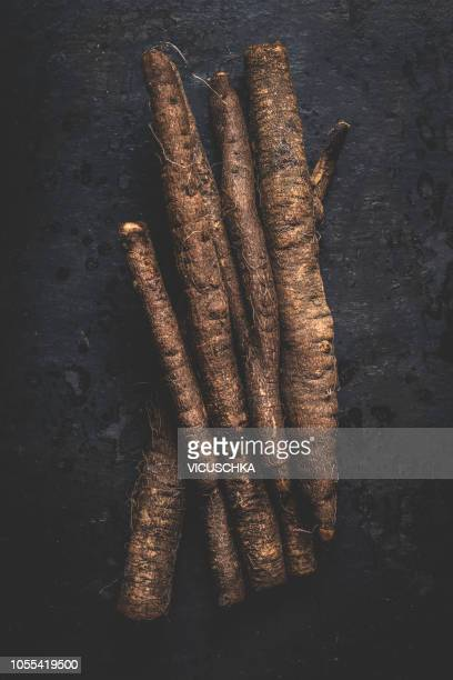Black salsify roots on dark background, top view