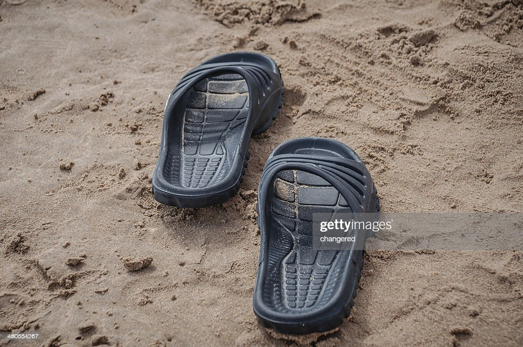 Black sandals on the beach sand : Stock Photo