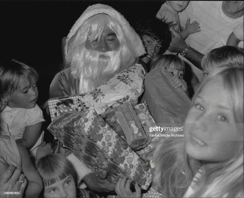 Black Santa (Syd Doc Cunningham) receiving presents outside the Christmas Tree in Martin Place tonight, for the Aboriginal Appeal. : News Photo