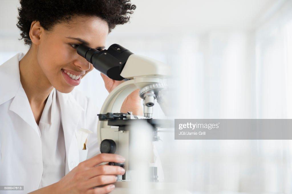 black-scientist-using-microscope-in-lab-