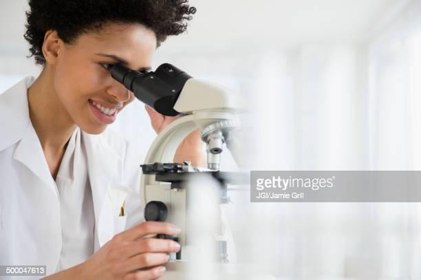 Black scientist using microscope in lab