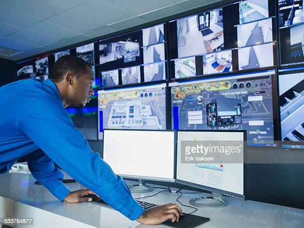 Black security officer watching surveillance cameras