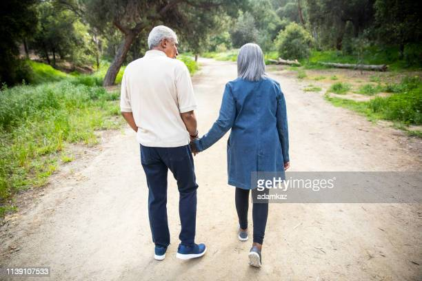 black senior couple walking in nature - natural parkland stock pictures, royalty-free photos & images