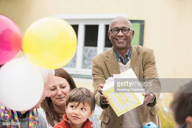 Black senior man giving birthday gift to his friend on his birthday, Bavaria, Germany