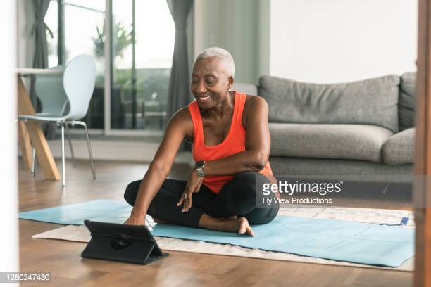 a black senior woman takes an online yoga class - exercising stock pictures, royalty-free photos & images
