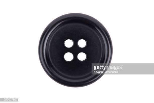 black sewing button isolated on white background - knoop naaigerei stockfoto's en -beelden