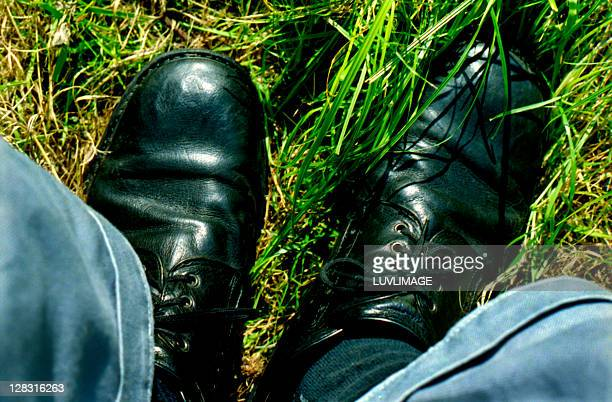 black shoes stand in the grass, bottom part of pants are visible