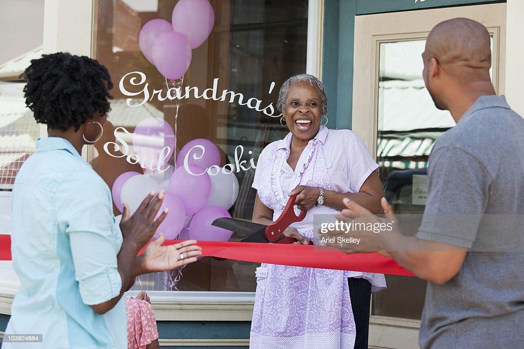 Black shopkeeper cutting ribbon at storefront : Stock Photo