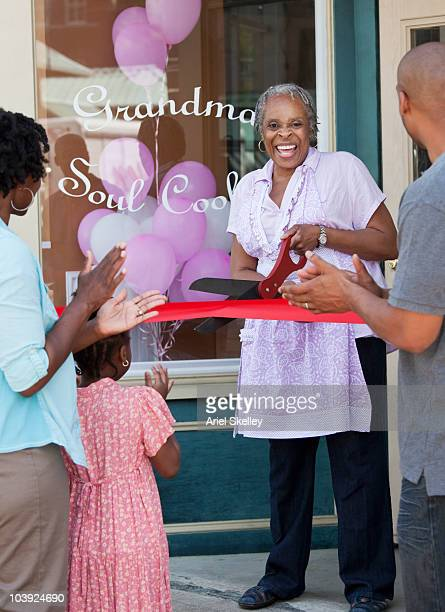 black shopkeeper cutting ribbon at storefront - ribbon cutting stock pictures, royalty-free photos & images