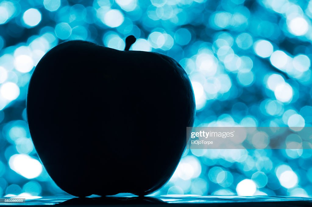 Black silhouette of a apple, blue bokeh background : Stock Photo
