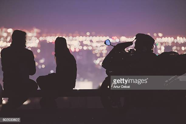 Black silhouettes of a young couple with his motorbike contemplating the Barcelona cityscape at night with bokeh lights.