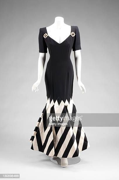 A black silk crepe short sleeve gown with black and white striped silk satin trumpet hem The gown features faux jeweled brooches at shoulders and...