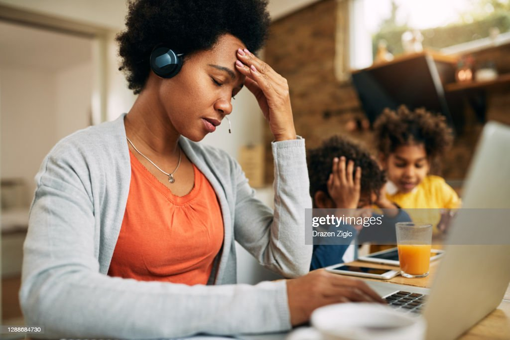 Black single mother feeling frustrated while working at home. : Stock Photo