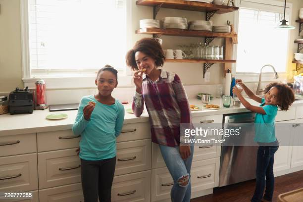 Black sisters eating food in domestic kitchen