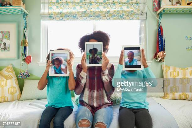 Black sisters hold digital tablet selfies over faces