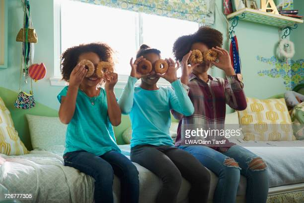 Black sisters holding donuts over eyes in bedroom