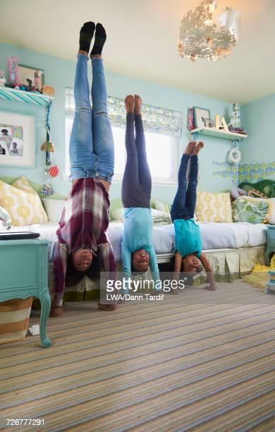 Black sisters performing handstands in bedroom