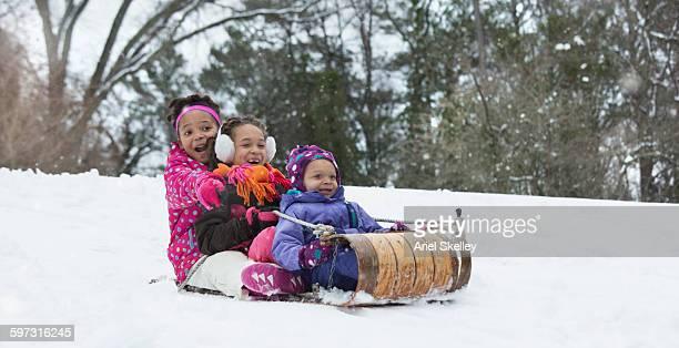Black sisters sledding in snow