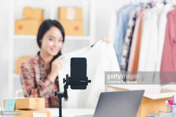 black smartphone with the stand is live selling the products with social media with the vendor and clothes in the background. sell online social media technology concept. - live broadcast stock pictures, royalty-free photos & images