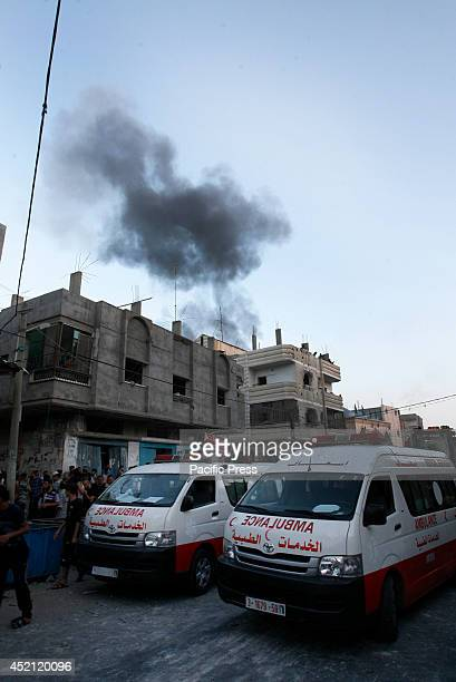 Black smoke ascends in the background from an Israeli air strike as Palestinians clear the rubble of the Ghanam family home after it was also...