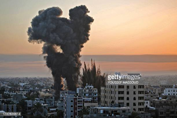 Black smoke billows after a series of Israeli airstrikes targeted Khan Yunis in the southern Gaza strip, early on May 12, 2021. - Israeli air raids...