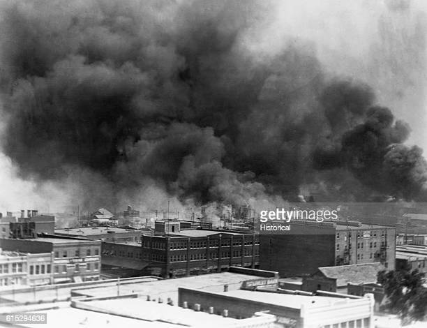 Black smoke billows from fires during the Tulsa Race Massacre of 1921, in the Greenwood District, Tulsa, Oklahoma, US, June 1921.