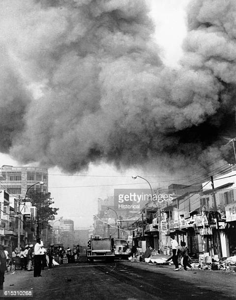 Black smoke covers areas of the capital city and fire trucks rush to the scenes of fires set during attacks by the Viet Cong during the festive Tet...