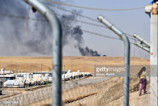 Black smoke from a burning oil facility can be seen behind the Debaga refugee camp between Mosul and Erbil Iraq 18 October 2016 According to Unicef...