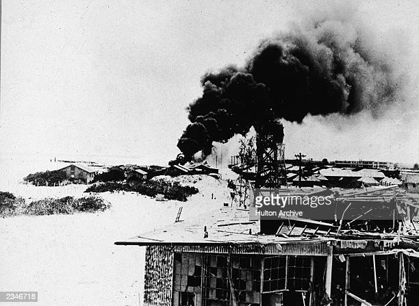 Black smoke pours from demolished buildings after Japanese air forces attacked the US Navy base on Midway Atoll the Battle of Midway World War II...